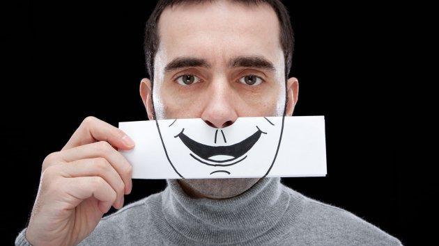 Изображение человека с нарисованной улыбкой. Фальш.